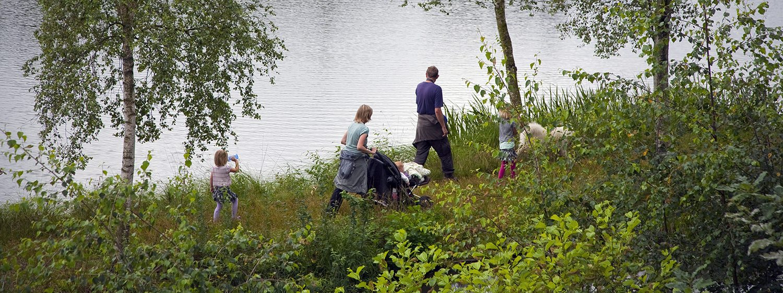 Børnefamilie går tur i en skov langs en sø.