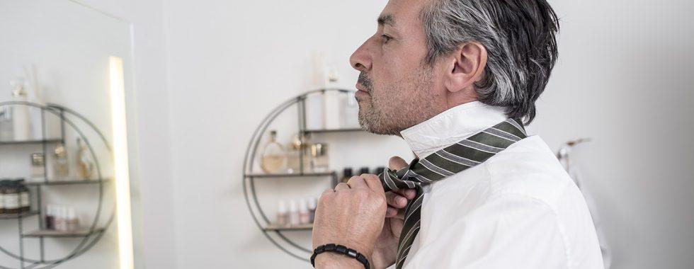 Forretningsmand binder hans slips i spejlet.