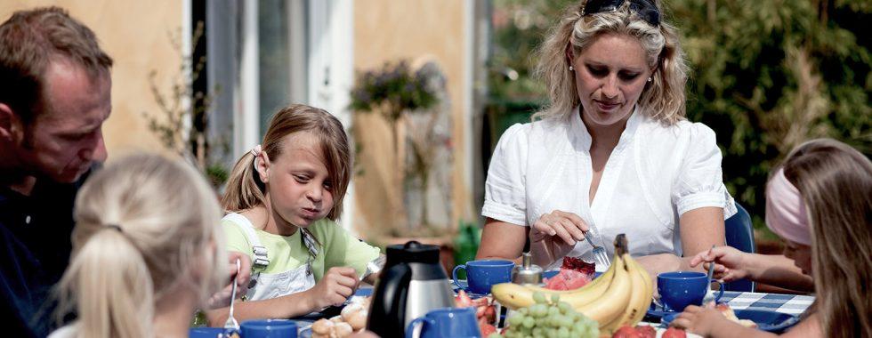 En familie sidder rundt om et morgenmadsbord, udenfor, en sommerdag