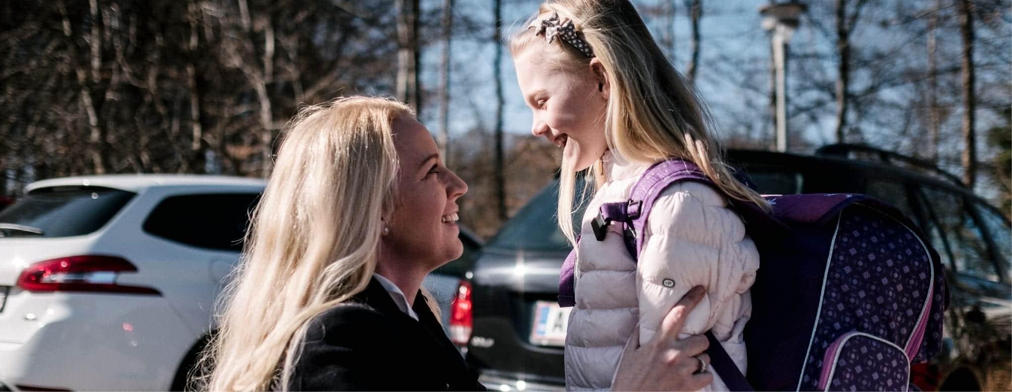 En mor siger farvel til sin datter, som er på vej i skole.